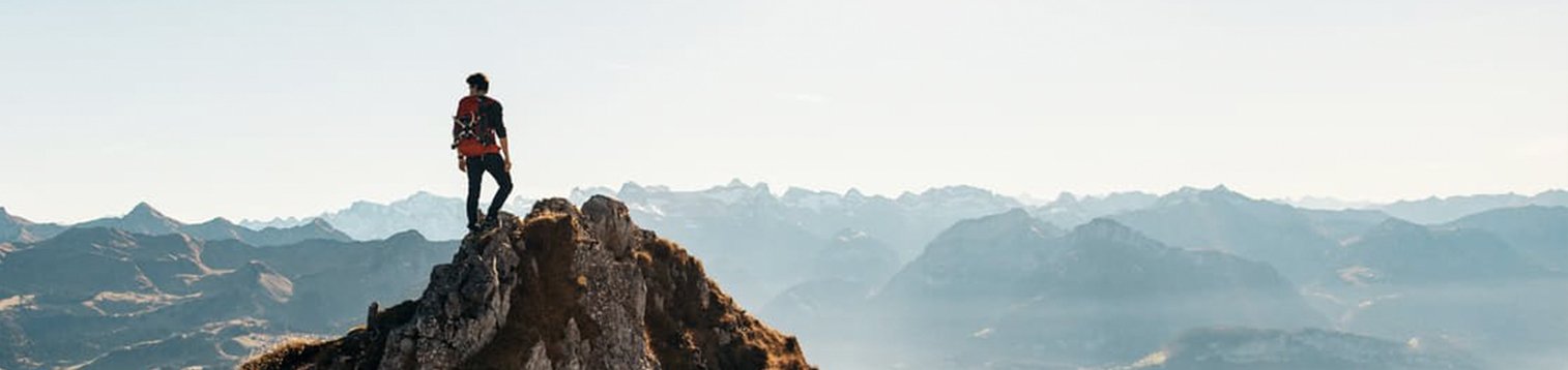 Traveller standing at the top of a mountain.